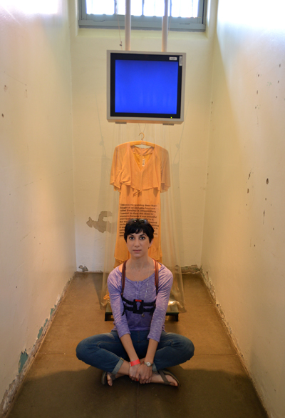 Sitting in a solitary confinement cell. Behind me is a display of a prisoners uniform.